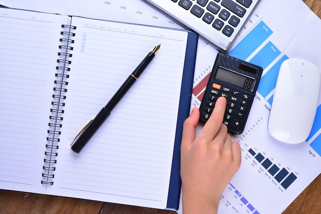 Ręka na kalkulatorze z wykresem, wykresem, klawiaturą, myszką na drewnianym stole