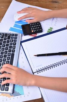Ręka na klawiaturze i myszy z wykresem, wykres na drewnianym stole