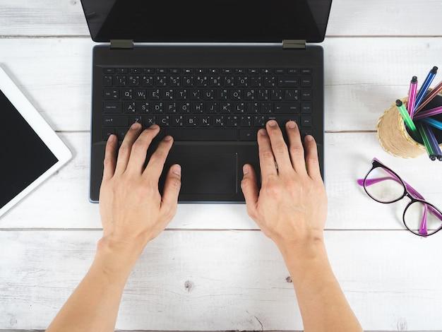 Ręka na klawiaturze laptopa z okularami i telefonem komórkowym na widoku z góry stołu
