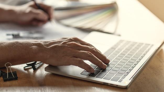 Ręka na komputerze twórczego myślenia architekta w architekturze nowoczesnego domu