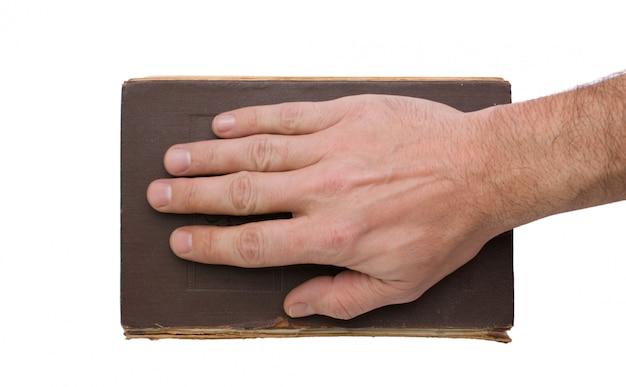Ręka na książce odizolowywającej na białym tle