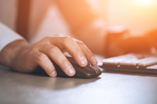 Ręka na myszy. koncepcja sukcesu w biznesie. mężczyzna w biurze. ciepły blask słońca światło dla teksta