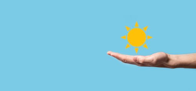 Ręka na niebieskiej powierzchni posiada symbol ikony słońca.