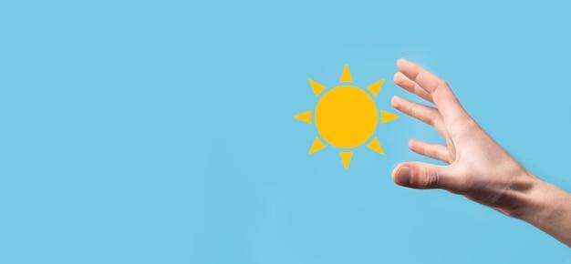 Ręka na niebieskim tle posiada symbol ikony słońca. zrównoważone źródło energii elektrycznej, koncepcja zasilania. ekologiczne podejście do technologii przyjaznej środowisku.