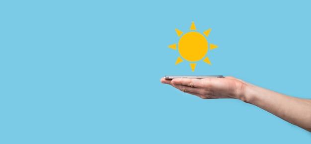 Ręka na niebieskim tle posiada symbol ikony słońca. zrównoważone źródło energii elektrycznej, koncepcja zasilania. podejście technologiczne przyjazne dla środowiska.
