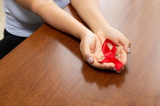 Ręka na stole trzymając czerwoną wstążkę. zapobieganie aids