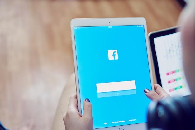Ręka naciska ekran facebook na apple ipad pro, media społecznościowe używają informacji