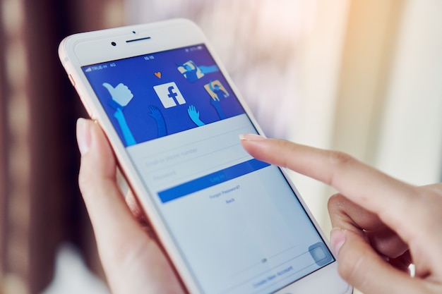 Ręka naciska ekran facebooka na apple iphone6, media społecznościowe.