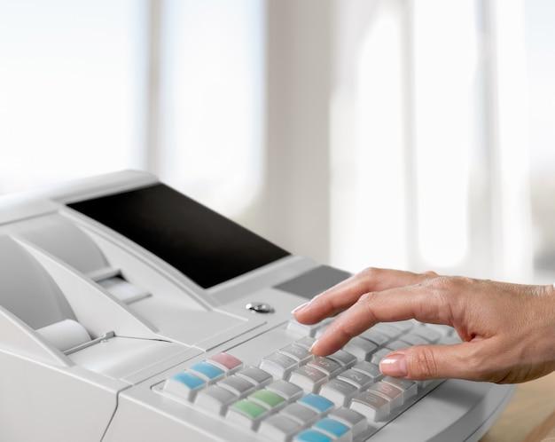 Ręka naciskając przycisk na kasie, widok z bliska