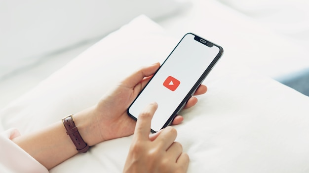 Ręka naciskająca na ekranie wyświetla ikony aplikacji youtube na apple iphone.