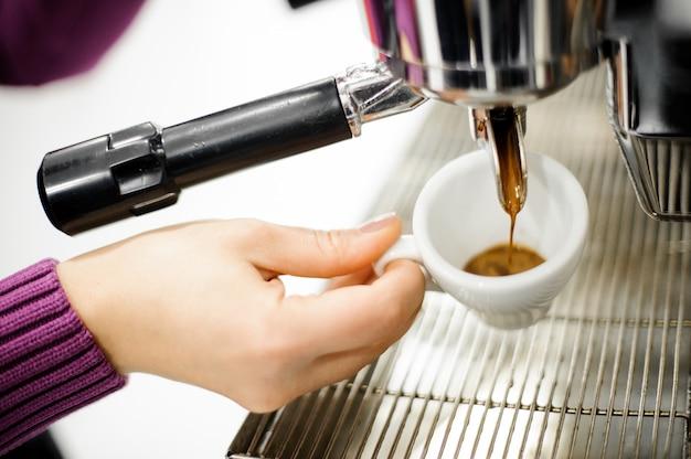Ręka nalewająca świeżą i aromatyczną kawę z ekspresu do kawy