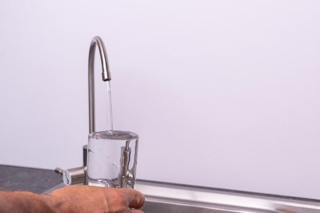 Ręka nalewająca szklankę wody z kranu z filtrem, biała ściana, miejsce na kopię
