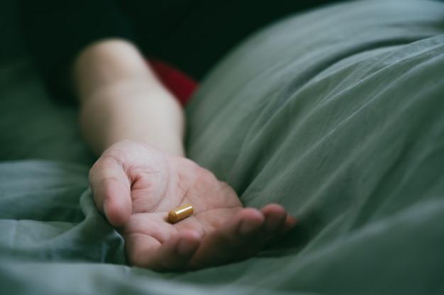 Ręka nastolatka azjatykci mężczyzna dolewania pigułki w jego rękę i dosypianie na łóżku