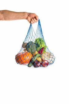 Ręka nie do poznania, trzymając worek mieszanych warzyw. koncepcja zdrowej żywności i zero odpadów. pojedynczo na białym.