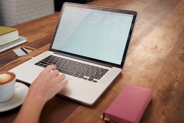 Ręka nierozpoznawalna kobieta pracuje na laptopie w kawiarni