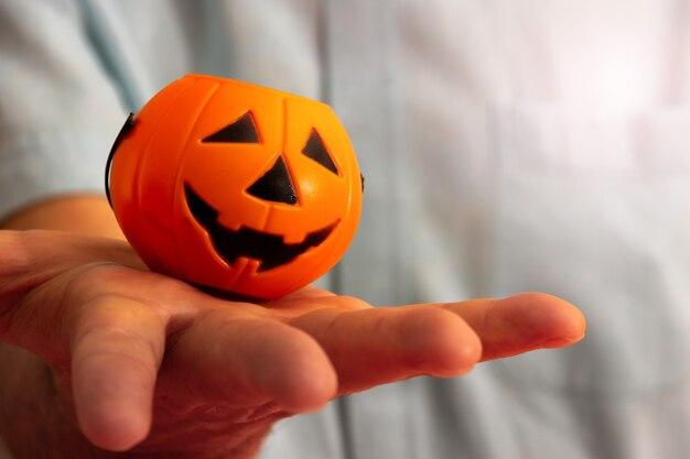 Ręka niosąca kosz cukierków halloween dyni. selektywne skupienie. skopiuj miejsce.