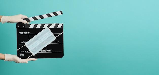 Ręka nosi białe rękawiczki medyczne i trzyma czarną tablicę clapper lub tablicę filmową z maską na twarz. ma zastosowanie w filmie, produkcji filmowej i przemyśle kinowym na niebieskim i zielonym tle.