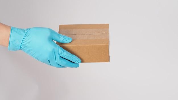 Ręka nosi niebieskie rękawiczki lateksowe i trzyma brązowe pudełko na białym tle.