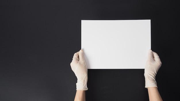 Ręka nosi rękawiczki i trzyma papier a4 na czarnym tle.
