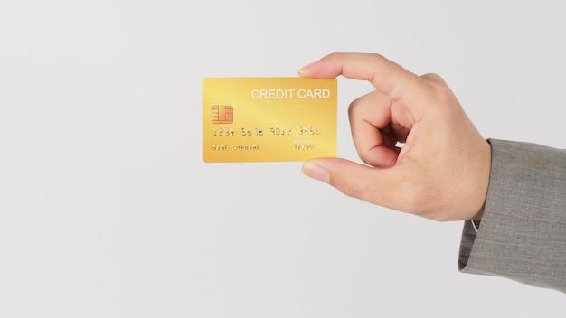 Ręka nosić szary garnitur trzyma złotą kartę kredytową na białym tle.
