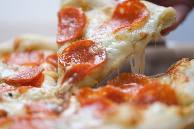 Ręka odrywająca kawałek pysznej pizzy z serem zbliżenie