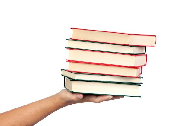 Ręka oferuje wiele książki odizolowywać na białym tle