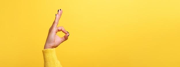 Ręka ok znak na żółtym tle trendu