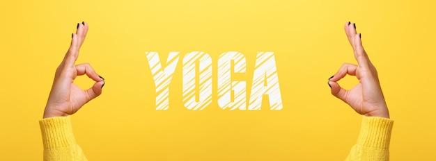 Ręka ok znak z napisem jogi na modnym żółtym tle, obraz panoramiczny