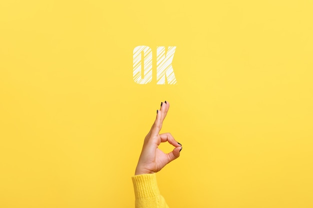 Ręka ok znak z napisem ok na modnym żółtym tle