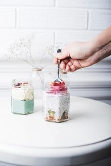 Ręka osoby biorąc smoothies owoce z łyżką