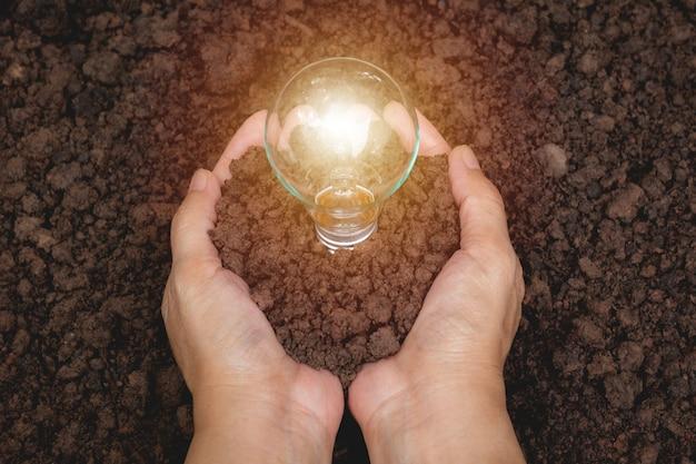 Ręka osoby mienia żarówka z ziemią dla pomysłu, sukcesu i energii słonecznej pojęcia ,.