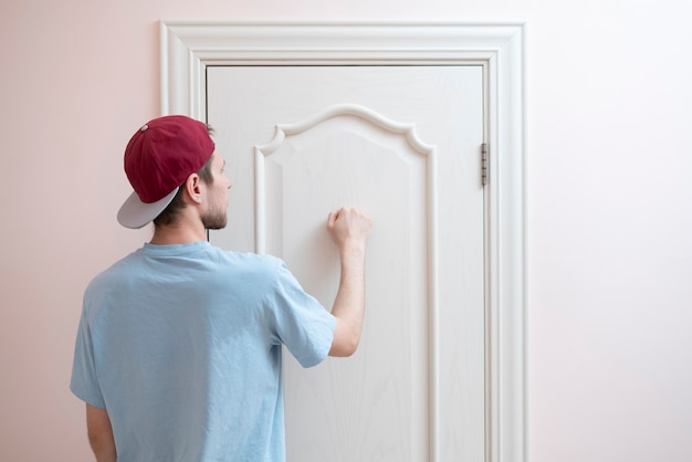 Ręka osoby puka do drzwi, odwiedza dom przyjaciół