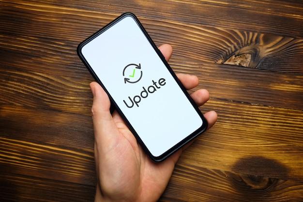 Ręka osoby trzyma smartfon po aktualizacji systemu.