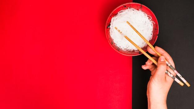 Ręka osoby używa pałeczek do zbierania smacznych makaronów na parze w misce nad podwójnym stołem