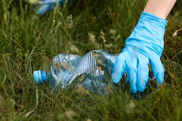 Ręka osoby w niebieskiej lateksowej rękawicy podnosi z ziemi plastikową butelkę