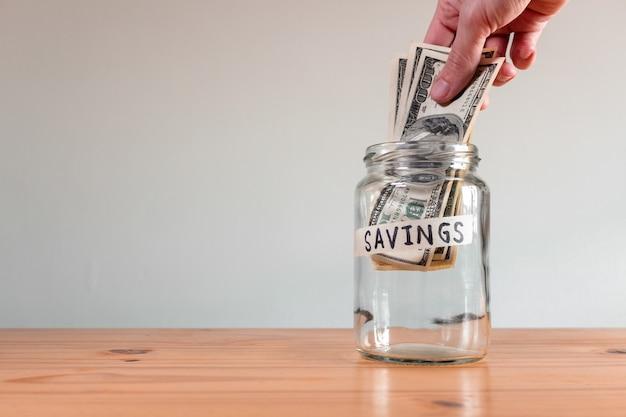 """Ręka osoby wkładającej banknoty dolarowe do szklanego słoika z napisem """"oszczędności"""""""
