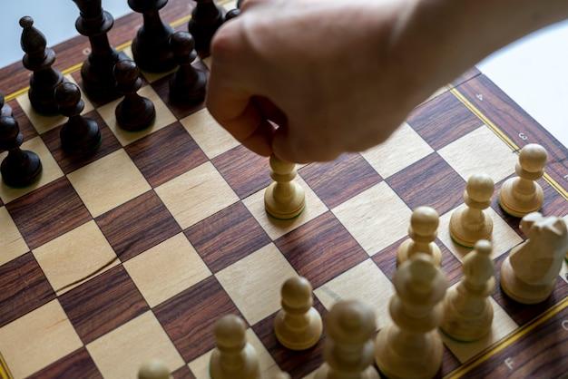 Ręka osoby wykonująca ruch w grze w szachy, myśląca o strategii