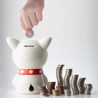 Ręka oszczędzania monety w skarbonka