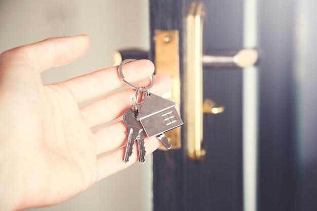 Ręka otwiera drzwi kluczem