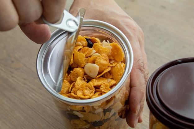 Ręka otwiera plastikową puszkę, azjatyckie słodkie przekąski, smaczne mieszane płatki kukurydziane, orzechy, winogrona i karmel na drewnianym tle naturalnego światła. pakowanie słodkich przekąsek z filiżanką herbaty
