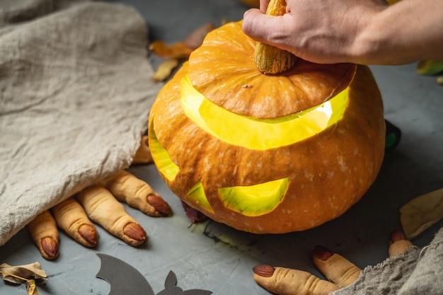 Ręka otwierająca dynię z twarzą wyciętą na halloween