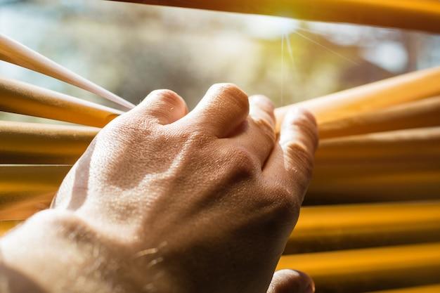 Ręka otwieranie listew żaluzji z palcem