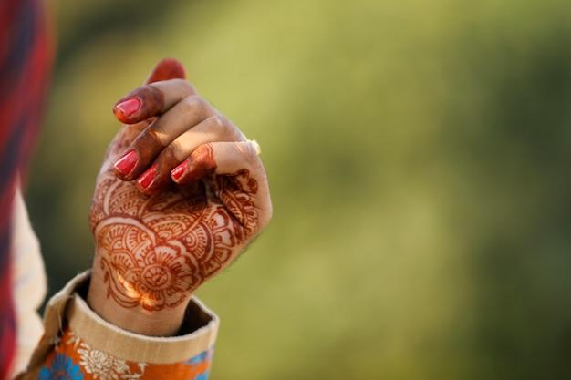 Ręka pana młodego z wzorem mehandi