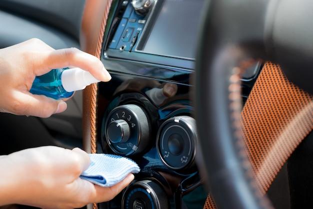 Ręka pani rozpylającej alkohol, środek dezynfekujący na klimatyzatorze w samochodzie, zapobiega infekcji covid 19