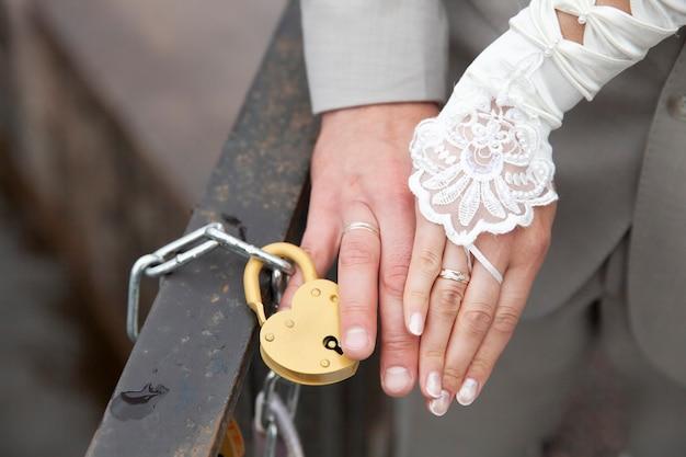 Ręka panny młodej i panny młodej, która zamknęła zamek w kształcie serca. ślub na zamówienie. zdjęcie wysokiej jakości