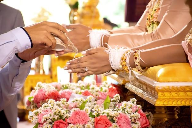Ręka panny młodej otrzymującej wodę święconą w tradycyjnej ceremonii ślubnej.