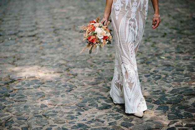 Ręka panny młodej trzyma od dołu bukiet ślubny