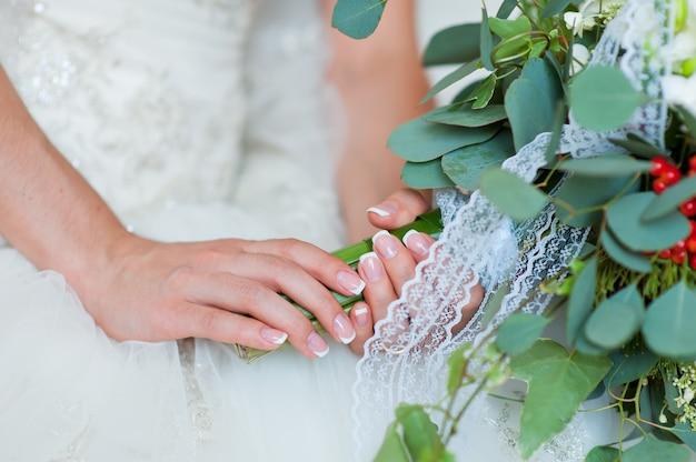 Ręka panny młodej z pierścieniem na zbliżenie bukiet.