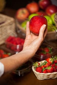 Ręka personelu płci żeńskiej trzyma jabłko