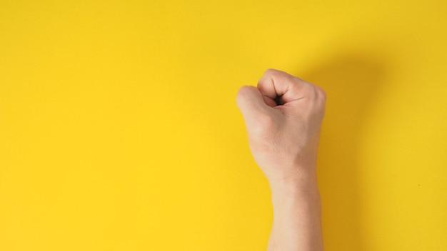 Ręka pięści jest izolowana na żółtym tle.